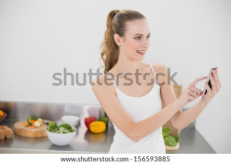 Smiling young woman sending a texting in the kitchen at home - stock photo