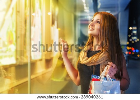 Smiling young woman shopping at an outdoor mall - stock photo
