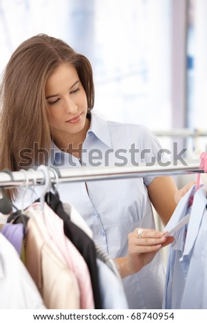 Smiling young woman shopping clothes, checking price tag on shirt.?