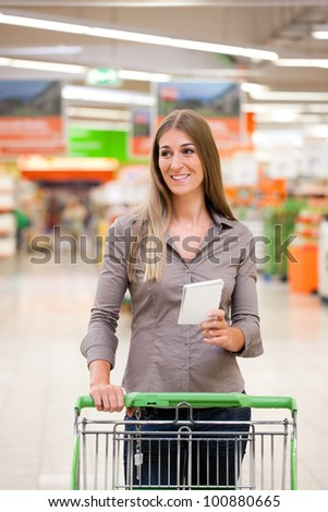 Smiling young woman shopping with trolley and checklist