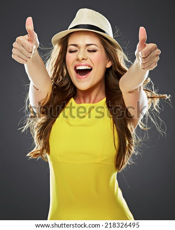 smiling young woman show thumb up . big toothy smile. long hair. yellow dress . - stock photo