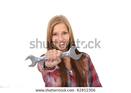 Smiling young woman showing a wrench into the camera - stock photo
