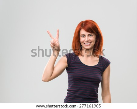 smiling young woman showing peace sign hand gesture, on grey background - stock photo