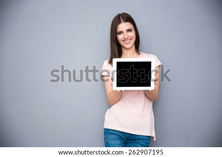 Smiling young woman showing tablet computer screen over gray background - stock photo