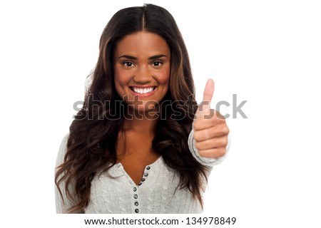 Smiling young woman showing thumbs up isolated over white background. - stock photo