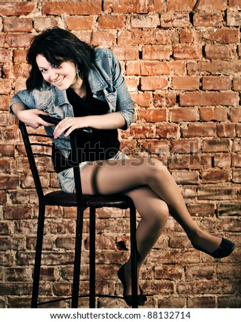 Smiling young woman sitting against brick wall background - stock photo