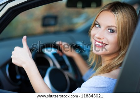 Smiling young woman sitting in car - stock photo