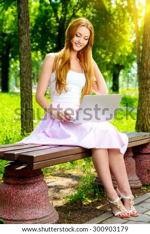 Smiling young woman sitting in the park on a sunny day and working on laptop. - stock photo