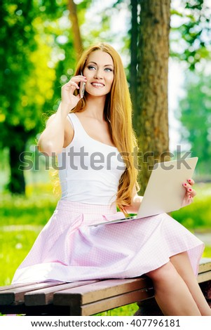 Smiling young woman sitting in the park on a sunny day, working on laptop and talking on the phone. - stock photo