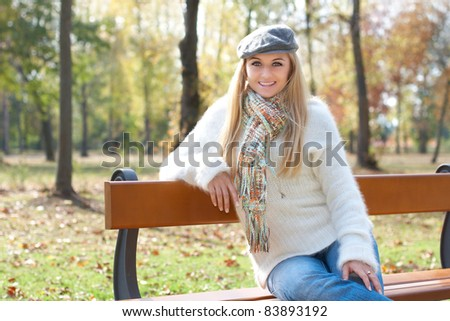 Smiling young woman sitting on a park bench. - stock photo