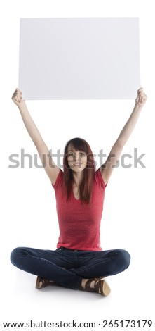 Smiling Young Woman Sitting on Floor with Legs Crossed, Raising an Empty White Cardboard, Emphasizing Copy Space. Isolated on White Background. - stock photo
