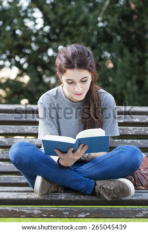 Smiling young woman sitting on old wood bench and reading blue book, outdoor. - stock photo