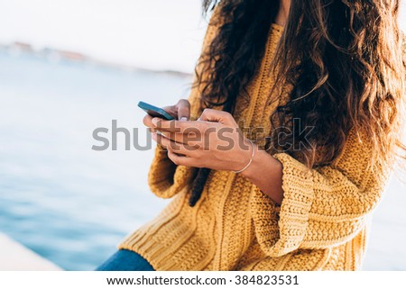 Smiling young woman sitting on pier and chatting over phone. Summertime - stock photo