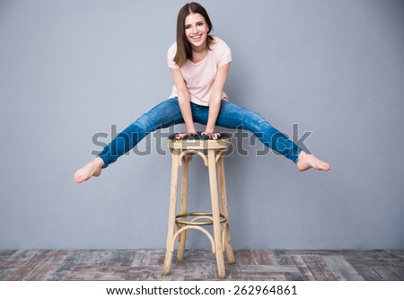 Smiling young woman sitting on the chair - stock photo
