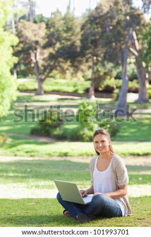 Smiling young woman sitting on the lawn with her laptop