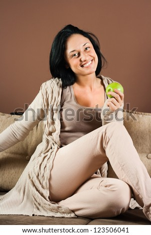 Smiling young woman sitting on the sofa with apple in her hand,Healthy eating - stock photo