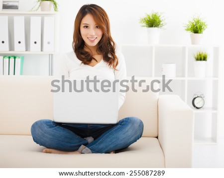 smiling Young woman sitting on the sofa with laptop - stock photo