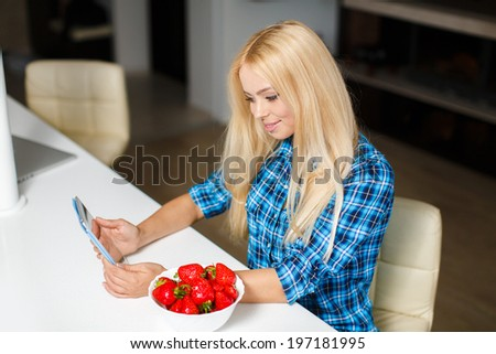 Smiling young woman sitting with laptop in modern kitchen with bowl strawberry - stock photo
