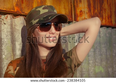 Smiling Young Woman Soldier in Camouflage Outfit - Portrait of a happy beautiful female army soldier  - stock photo
