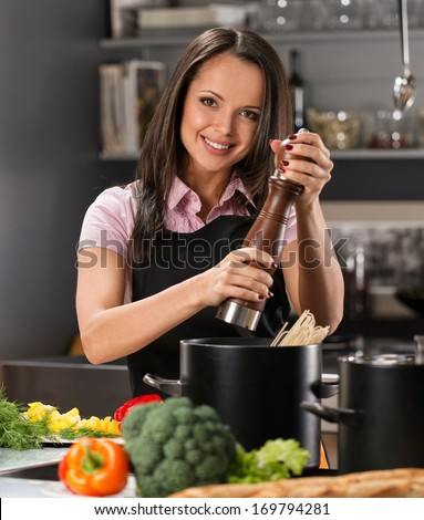 Smiling young woman spices to pot on a modern kitchen