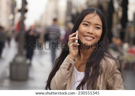 Smiling young woman standing on the street and talking on the phone.  - stock photo
