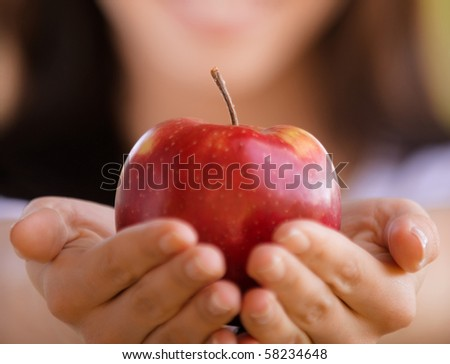 Smiling young woman stretches red apple - stock photo