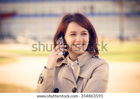 Smiling young woman student talking on mobile phone using tablet in campus university.Young smiling student outdoors talking to phone.