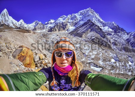 Smiling young woman takes a selfie  on mountain peak ,Everest region, Nepal - stock photo