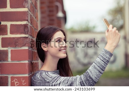 Smiling young woman taking a selfie on her mobile phone as she poses against an exterior brick wall, profile view - stock photo