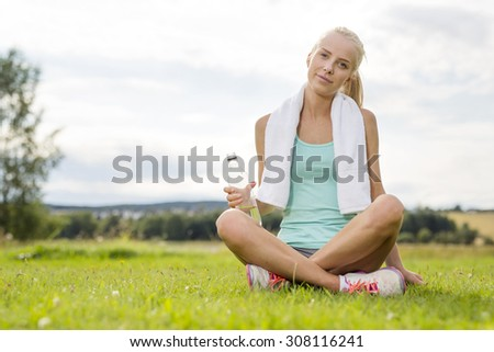 Smiling young woman taking break on the grass - stock photo