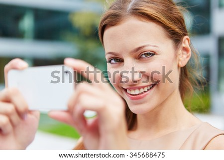 Smiling young woman taking pictures with her smartphone in the city - stock photo