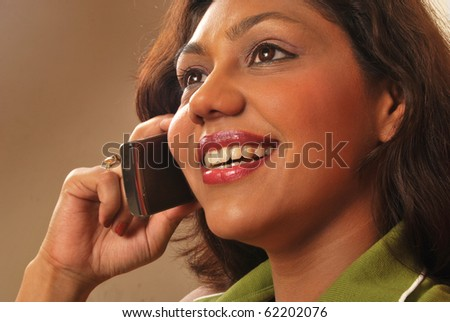 smiling young woman talking on mobile phone - stock photo