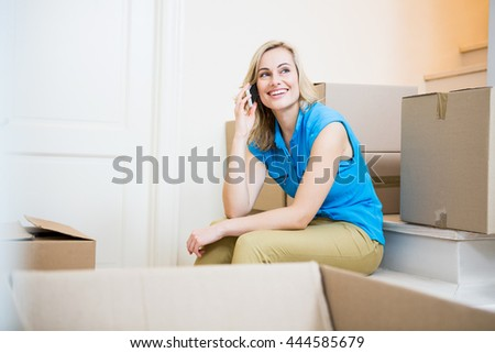 Smiling young woman talking on mobile phone in new house - stock photo