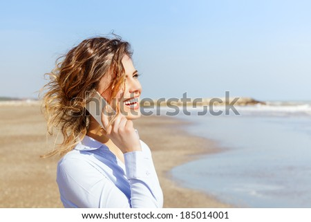 Smiling young woman talking on the mobile phone at the seaside - stock photo