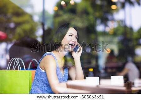 smiling young woman talking on the phone in cafe shop - stock photo