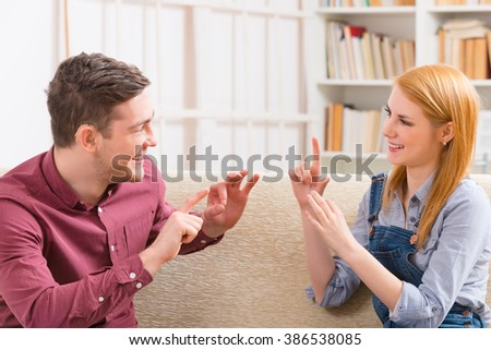 Smiling young woman talking using sign language with her hearing impairment man - stock photo