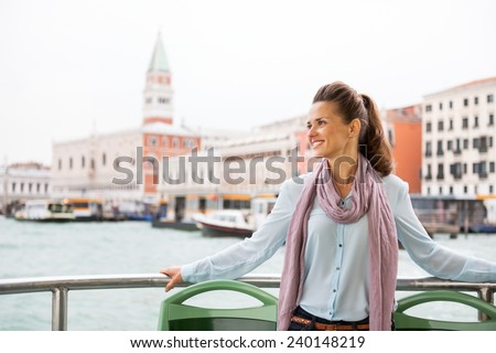 Smiling young woman travel by vaporetto in venice, italy - stock photo