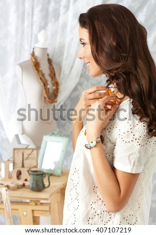 Smiling young woman trying on pearl necklace at retro home. Side view. - stock photo
