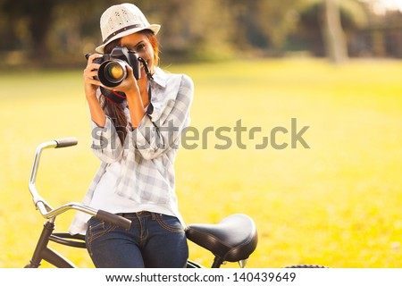 smiling young woman using a camera to take photo outdoors at the park - stock photo