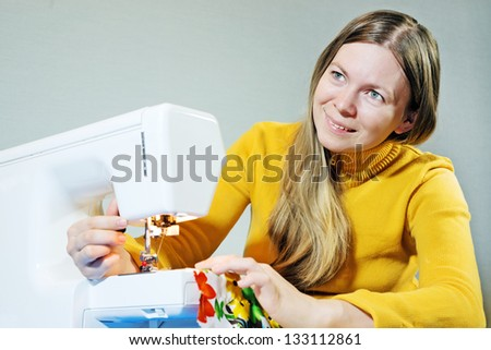 Smiling young woman using a sewing machine to sew up - stock photo