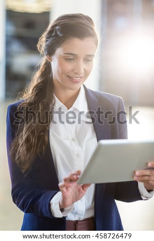 Smiling young woman using digital tablet in office