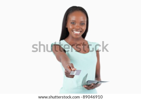 Smiling young woman using her credit card to pay against a white background - stock photo