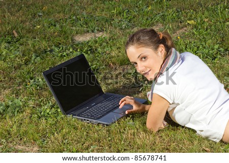 Smiling young woman using laptop on grass