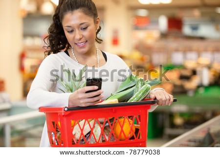 Smiling young woman using mobile phone while shopping in shopping store - stock photo