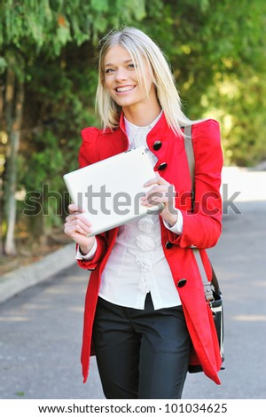 Smiling young woman using tablet PC outdoors - stock photo