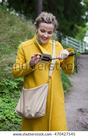 Smiling young woman watching pictures in the smartphone screen