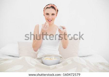 Smiling young woman watching television while eating popcorn and sitting on her bed - stock photo