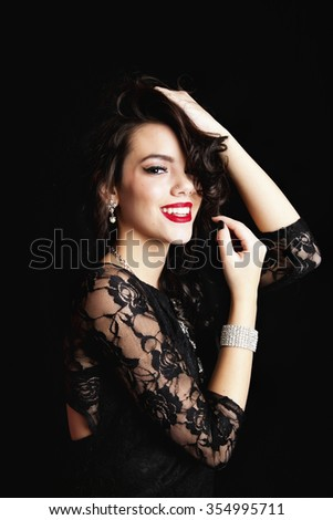 Smiling young woman wearing a classic black lace dress and crystal jewelery with hands up in her hair.  Shot on black background. - stock photo