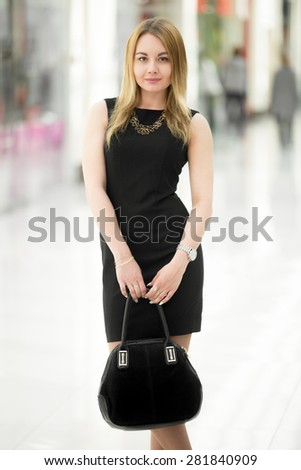 Smiling young woman wearing short black dress holding suede handbag in modern building - stock photo