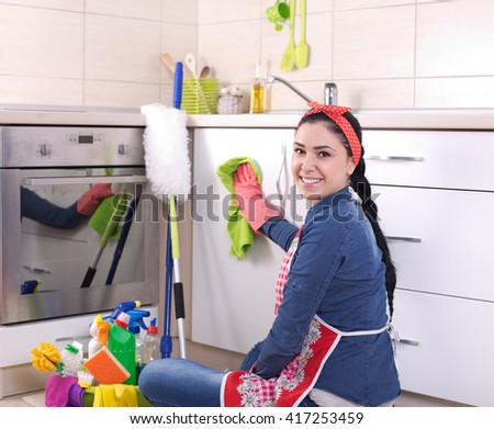 Smiling young woman wiping kitchen furniture with green cloth and looking at camera over shoulder - stock photo